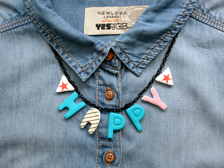 Alphabet necklace worn with a denim shirt