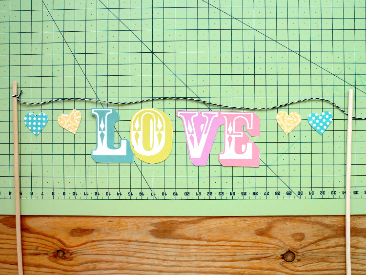 Attaching the letters and hearts to the bakers twine