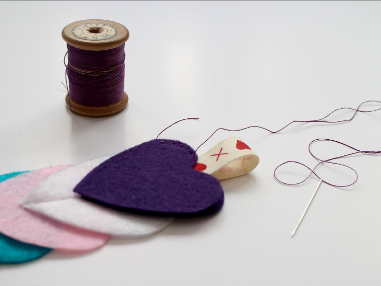Stitching the felt hearts and ribbon in place