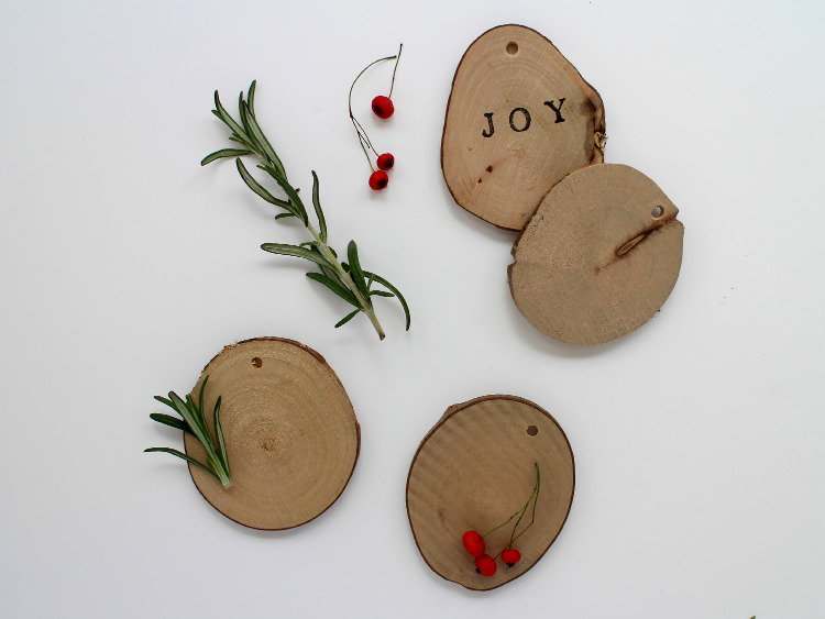 Wooden disc decorations with berries and rosemary